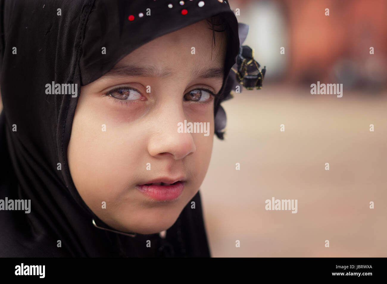 NEW DELHI, INDIA. MAY 31,2017: A young Muslim girl looks on as she along with her family sit in Jama Masjid.They - Stock Image