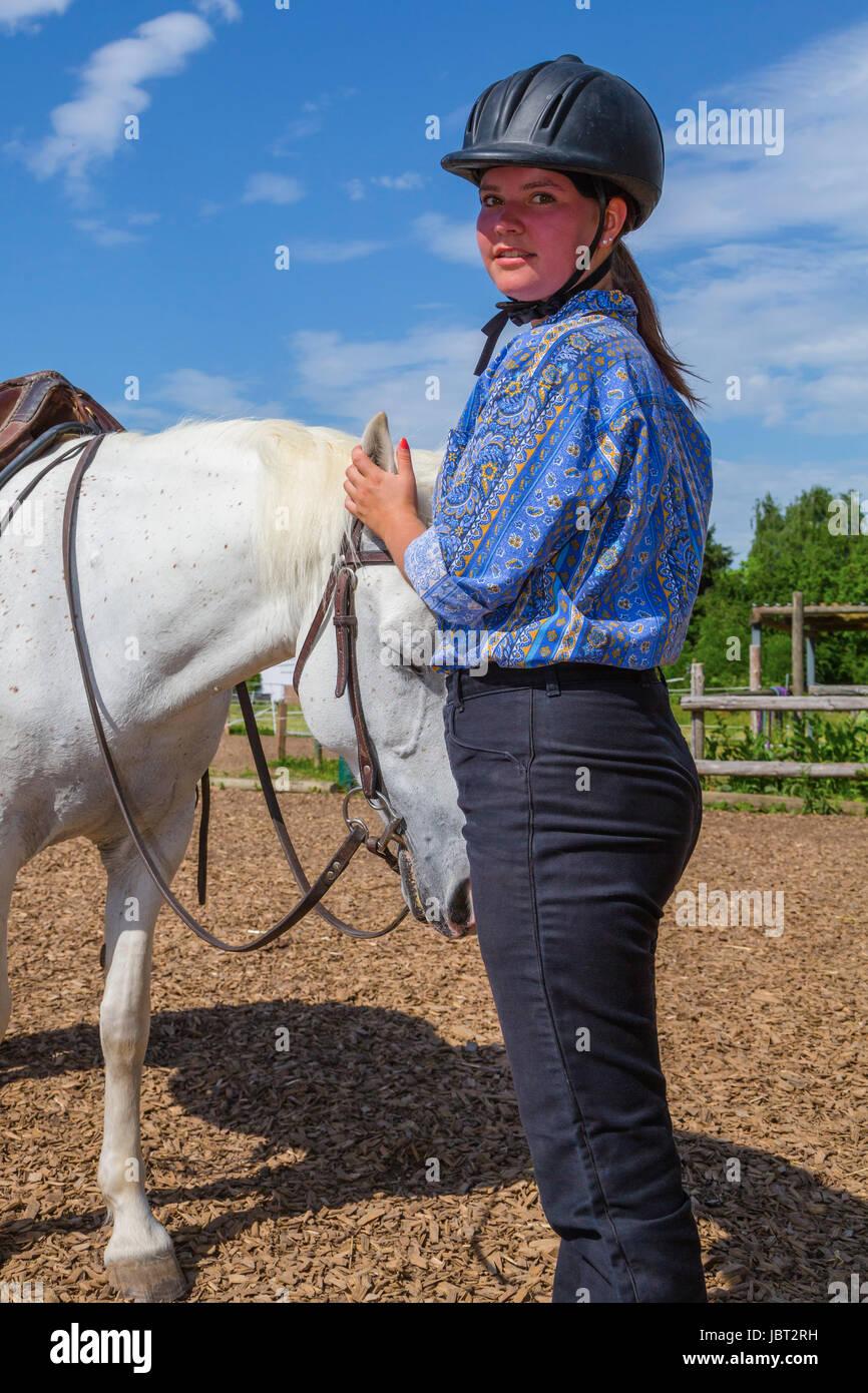 Junge Frau streichelt weisses Pferd Stock Photo