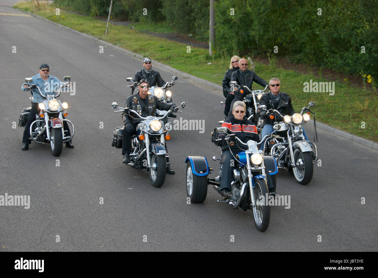 A group of Harley Davidson motorcycle and riders on the road - Stock Image