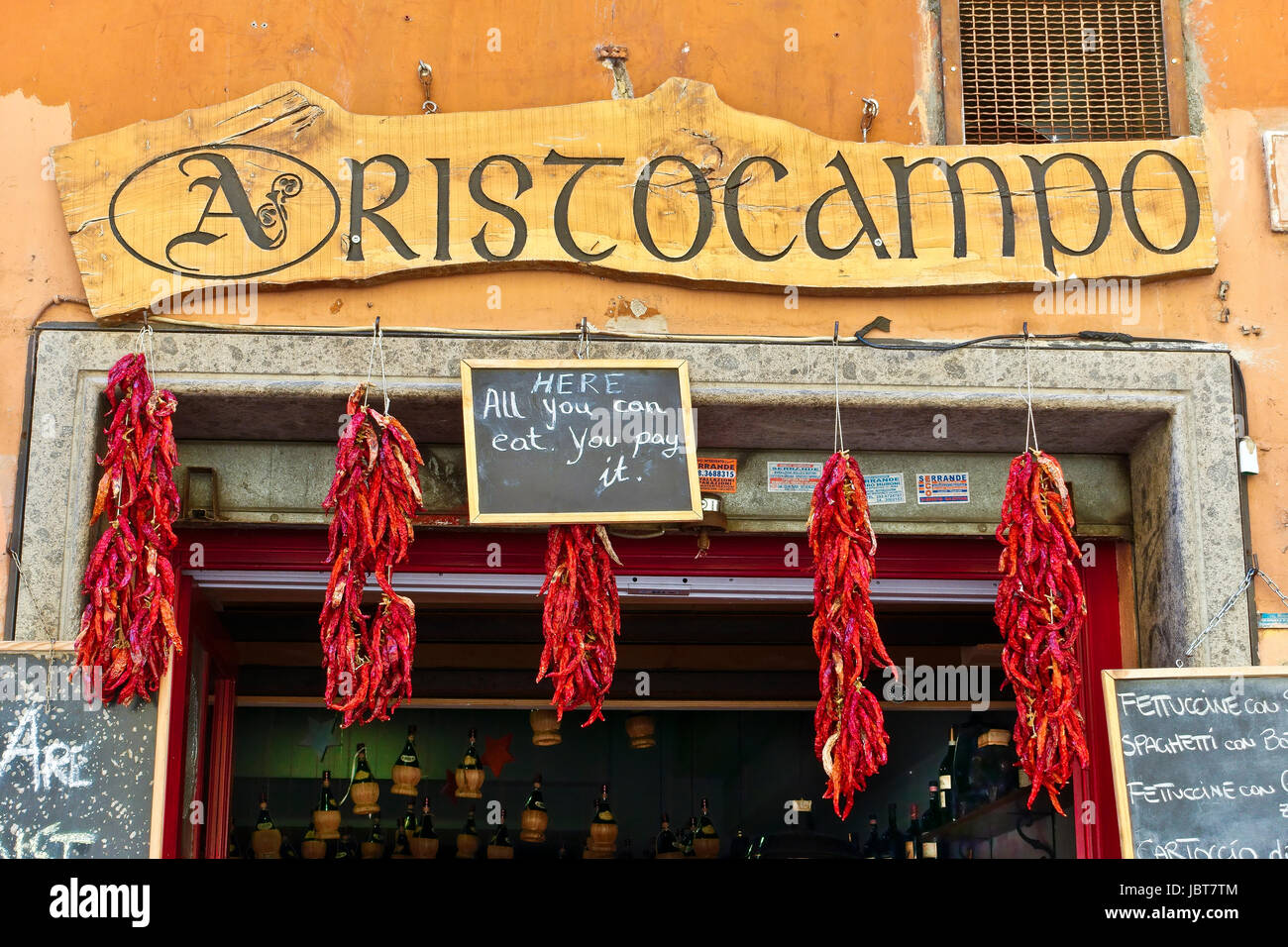 Restaurant in a alley in Trtastevere, typical characteristic roman borough. Restaurant sign and hung red chili peppers. - Stock Image