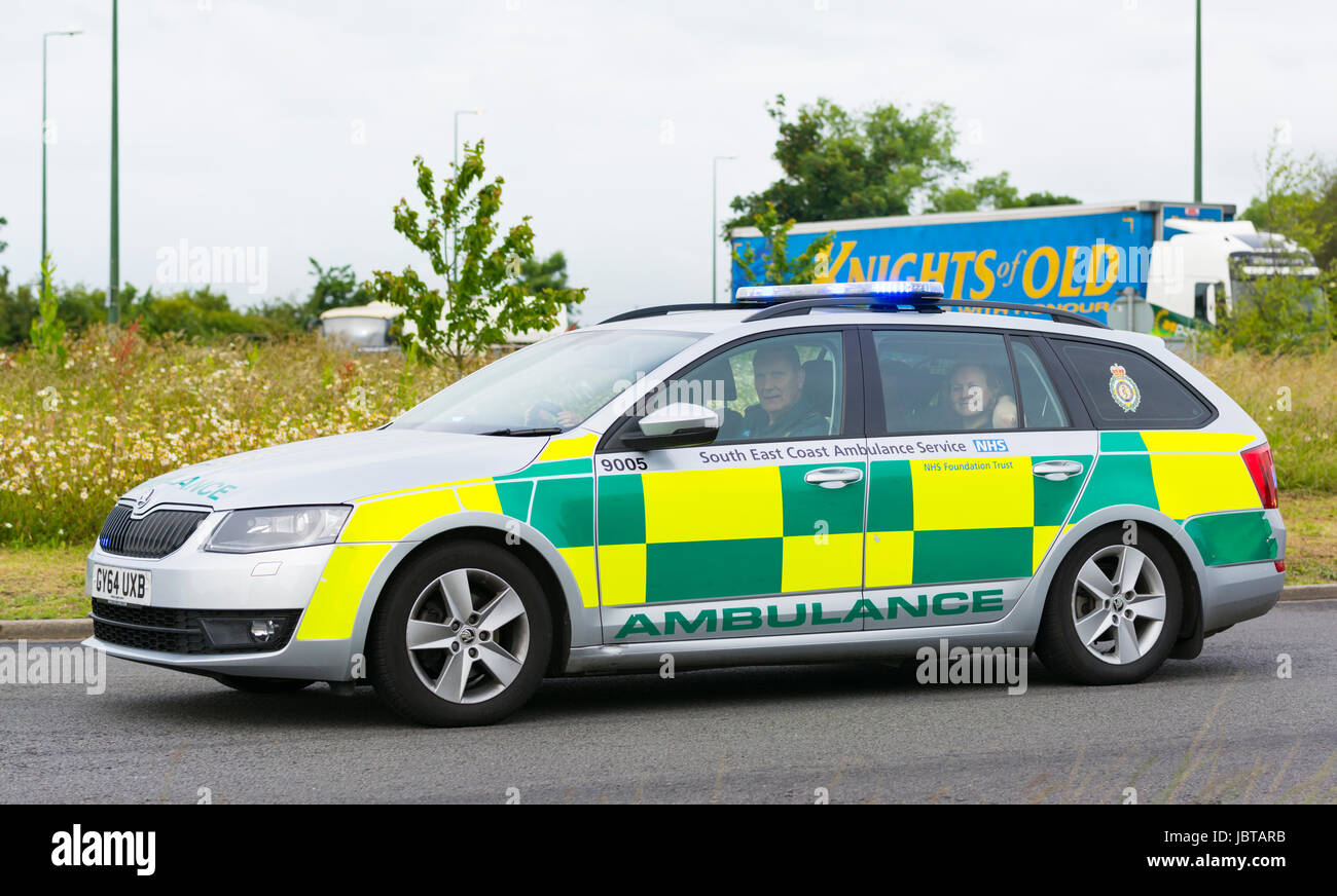 South East Coast Ambulance car speeding on a roundabout with blue lights on in the UK. Stock Photo