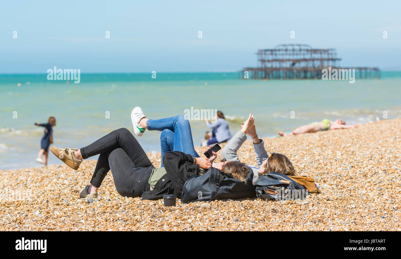 Young women laying on a beach using smartphones. - Stock Image