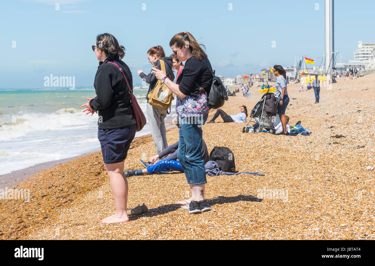 Group of women standing on a beach at the seaside using mobile phones. - Stock Image