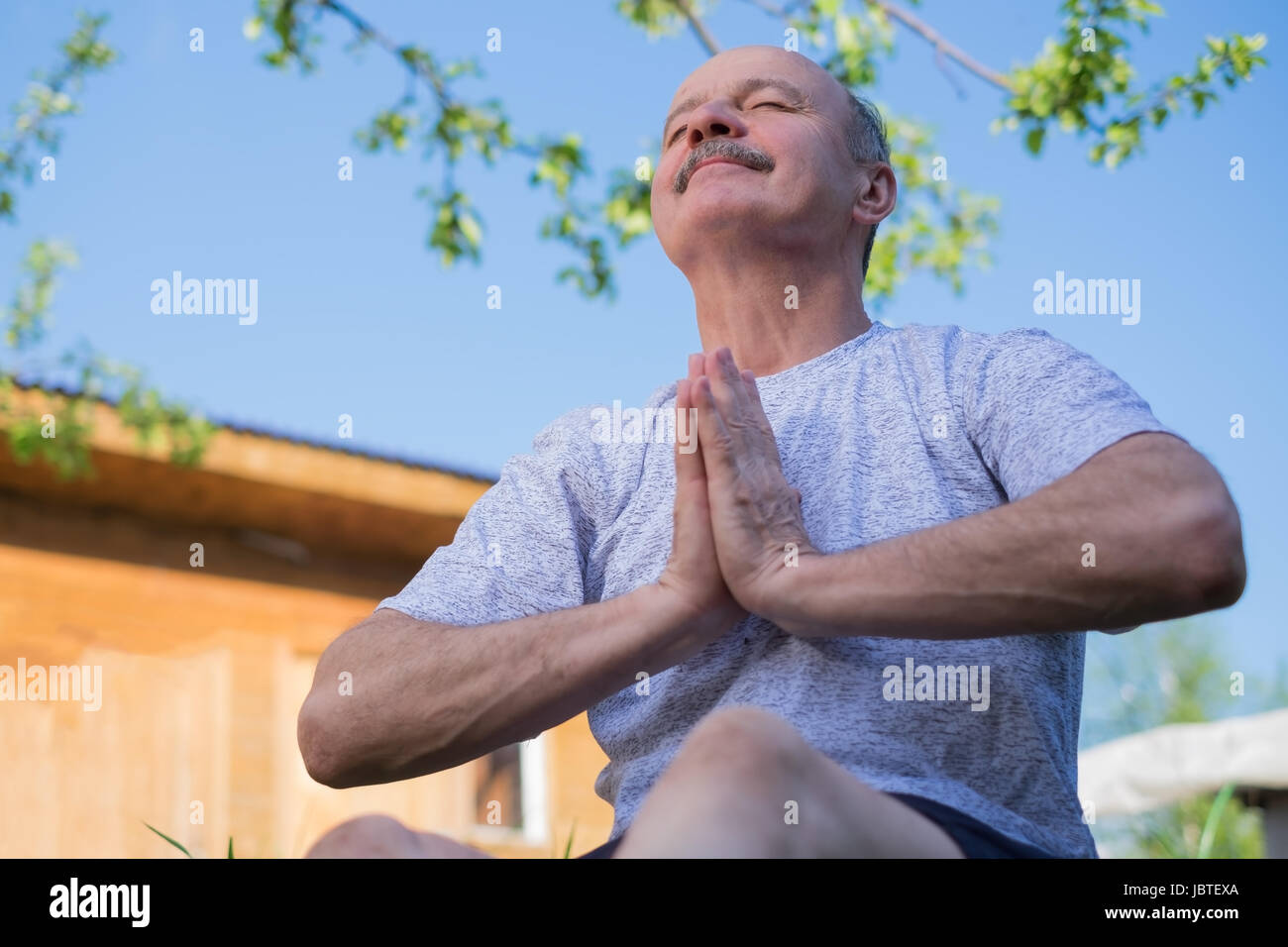 Senior man with mustache with namaste sitting.Concept of calm and meditation. - Stock Image