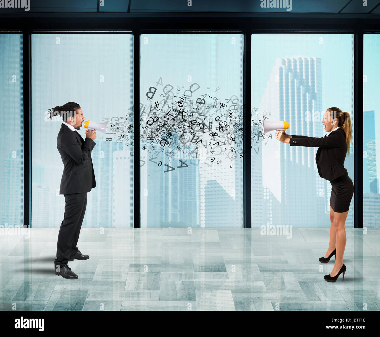 Two collegues screaming each other with megaphone in office - Stock Image