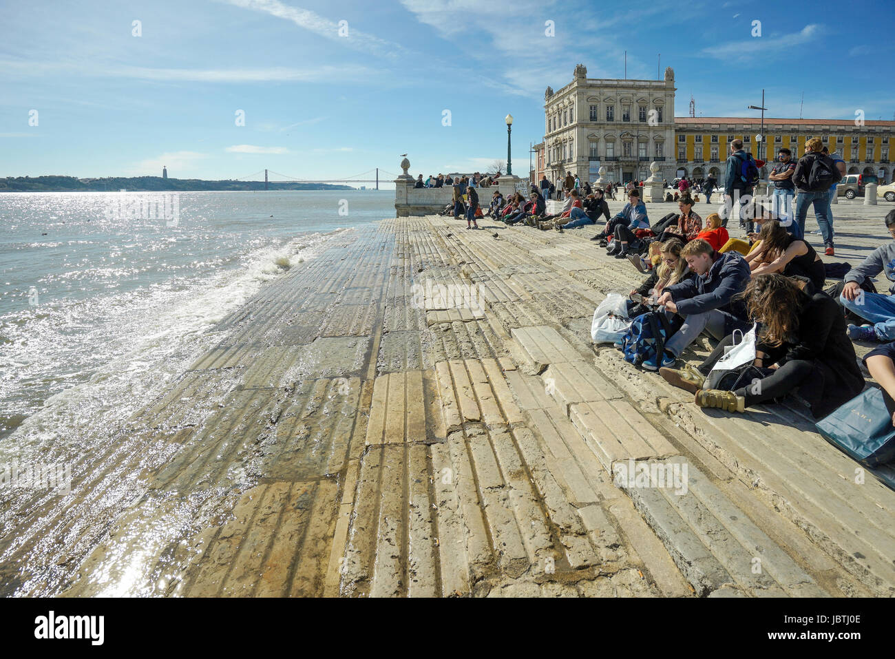 Europe, Portugal, Lisbon, young people sit in the bank promenade in the Tejo river                   , Europa, Lissabon, - Stock Image
