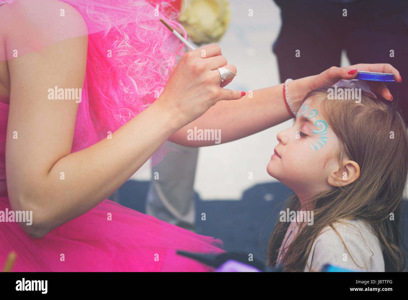 Little girl getting her face painted - Stock Image