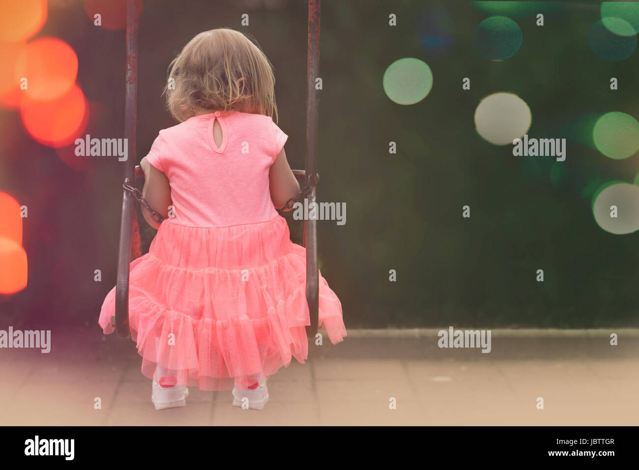 Little girl in beautiful pink dress swinging - Stock Image