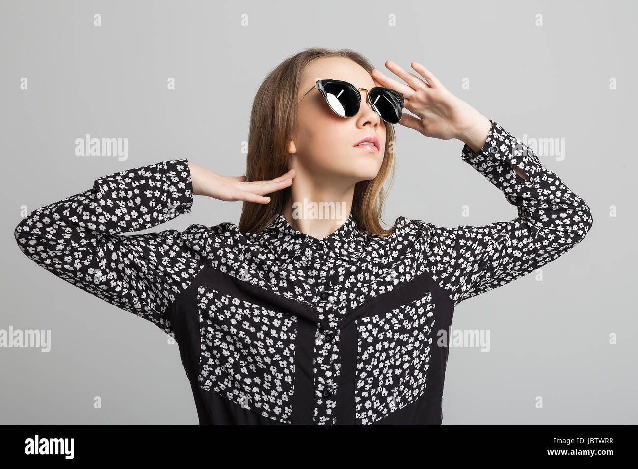 085cbefc787 Portrait of young pretty girl with black round sunglasses over gray  background. woman dressed in