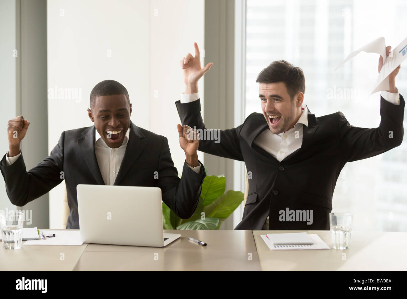 Two happy businessmen in suits raising hands near laptop, multicultural business group celebrate victory, stock - Stock Image