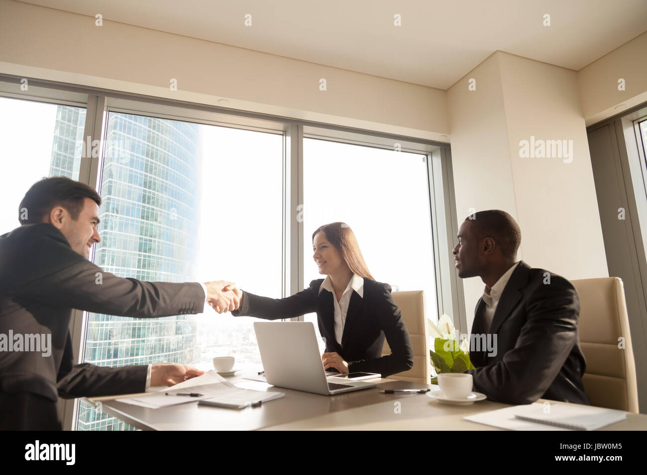 Cheerful female and male caucasian partners handshaking over office desk, multi-ethnic meeting with afro american - Stock Image