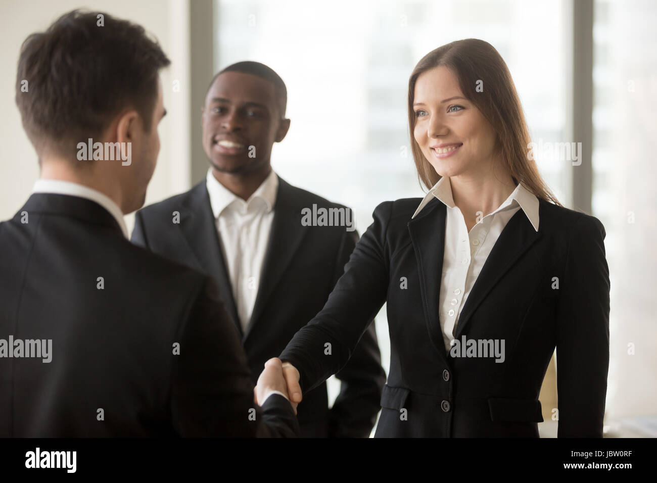 Beautiful smiling businesswoman and businessman handshaking standing in office, nice to meet you, first impression, - Stock Image