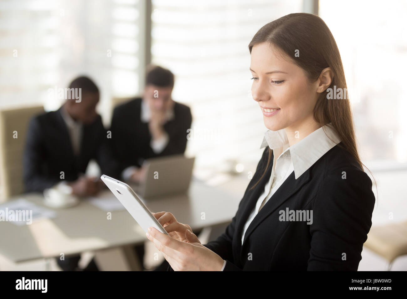 Young attractive businesswoman holding tablet, looking at screen, standing in office with colleagues at background, - Stock Image