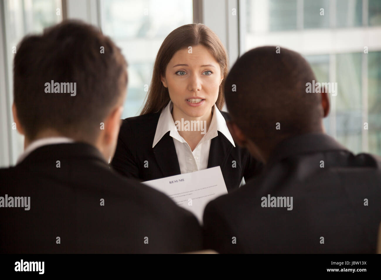 Female applicant introducing herself during job interview, talking about working experience, rear view at multiracial - Stock Image