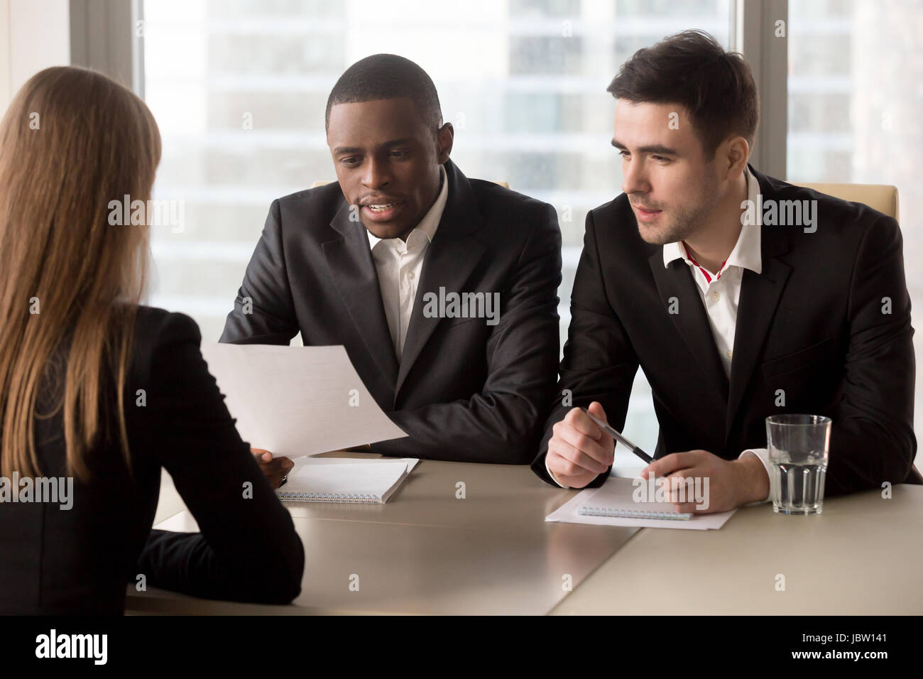 Multiracial black and white recruiters, executive hr management group interviewing female job applicant, headhunters - Stock Image