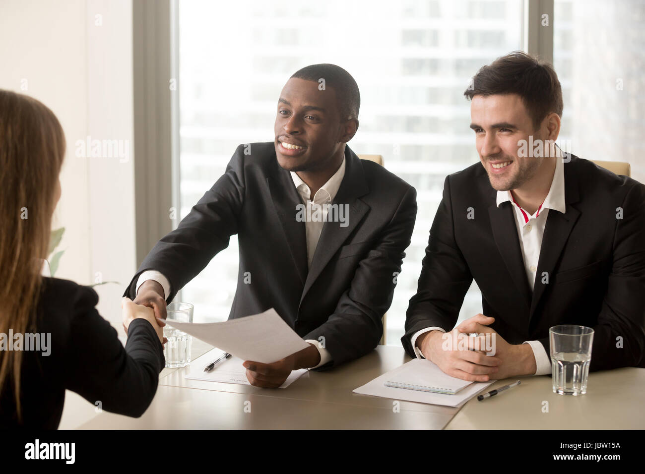 Two cheerful black and white recruiters welcoming female applicant on job interview, african and caucasian hr managers - Stock Image