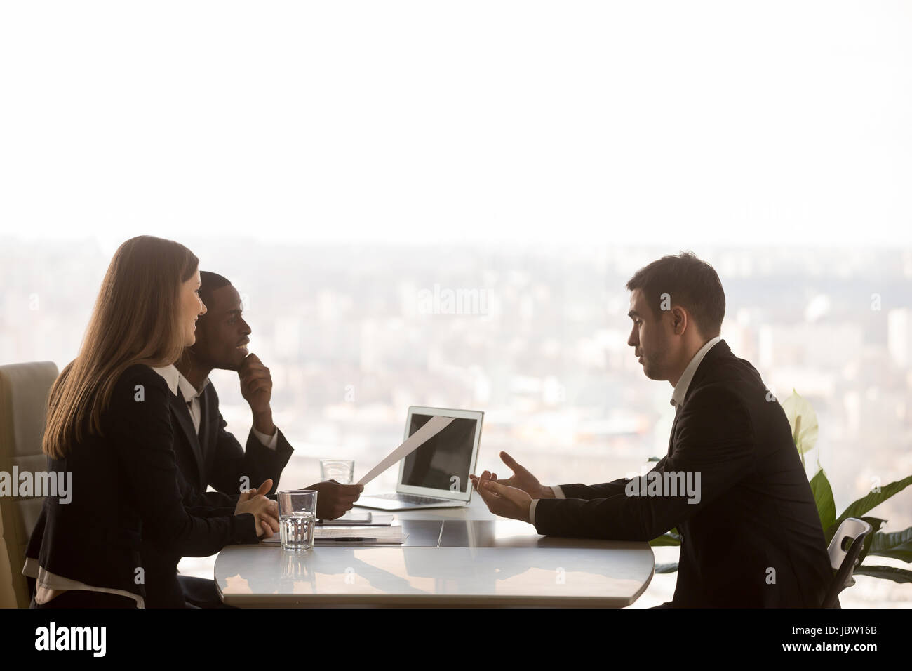 Friendly attentive hr managers interviewing vacancy applicant, multi-ethnic partners discussing new project idea - Stock Image