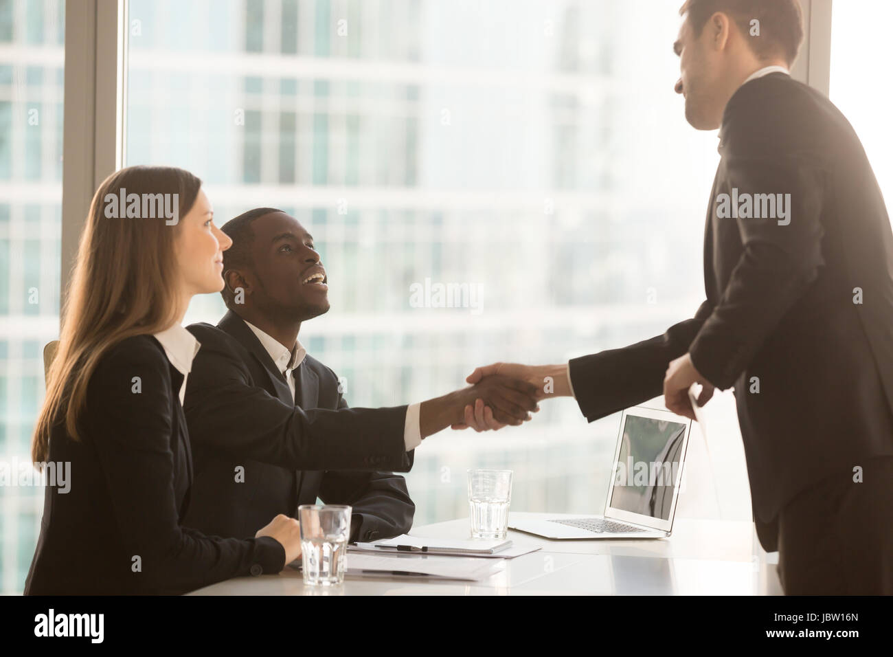 Friendly black and white recruiters sitting at office desk shaking hands with applicant just arrived for interview, Stock Photo