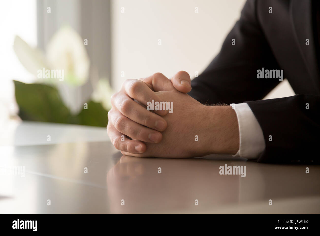 Close up of male clasped hands clenched together on table, businessman preparing for job interview, concentrating - Stock Image