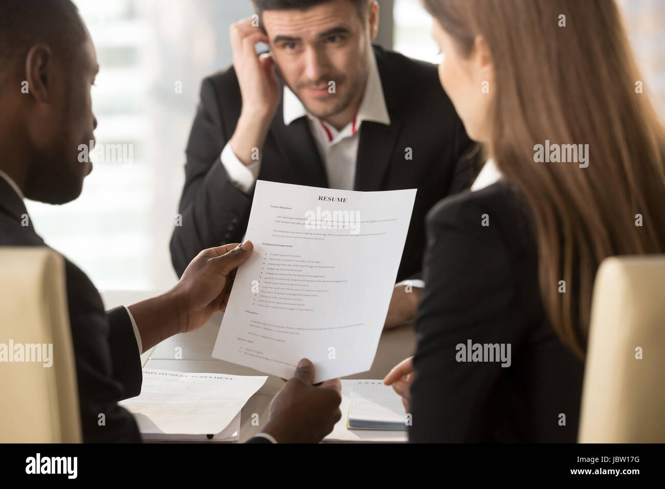 Employers or recruiters holding reviewing bad poor cv of unemployed worried nervous applicant waiting for result, - Stock Image