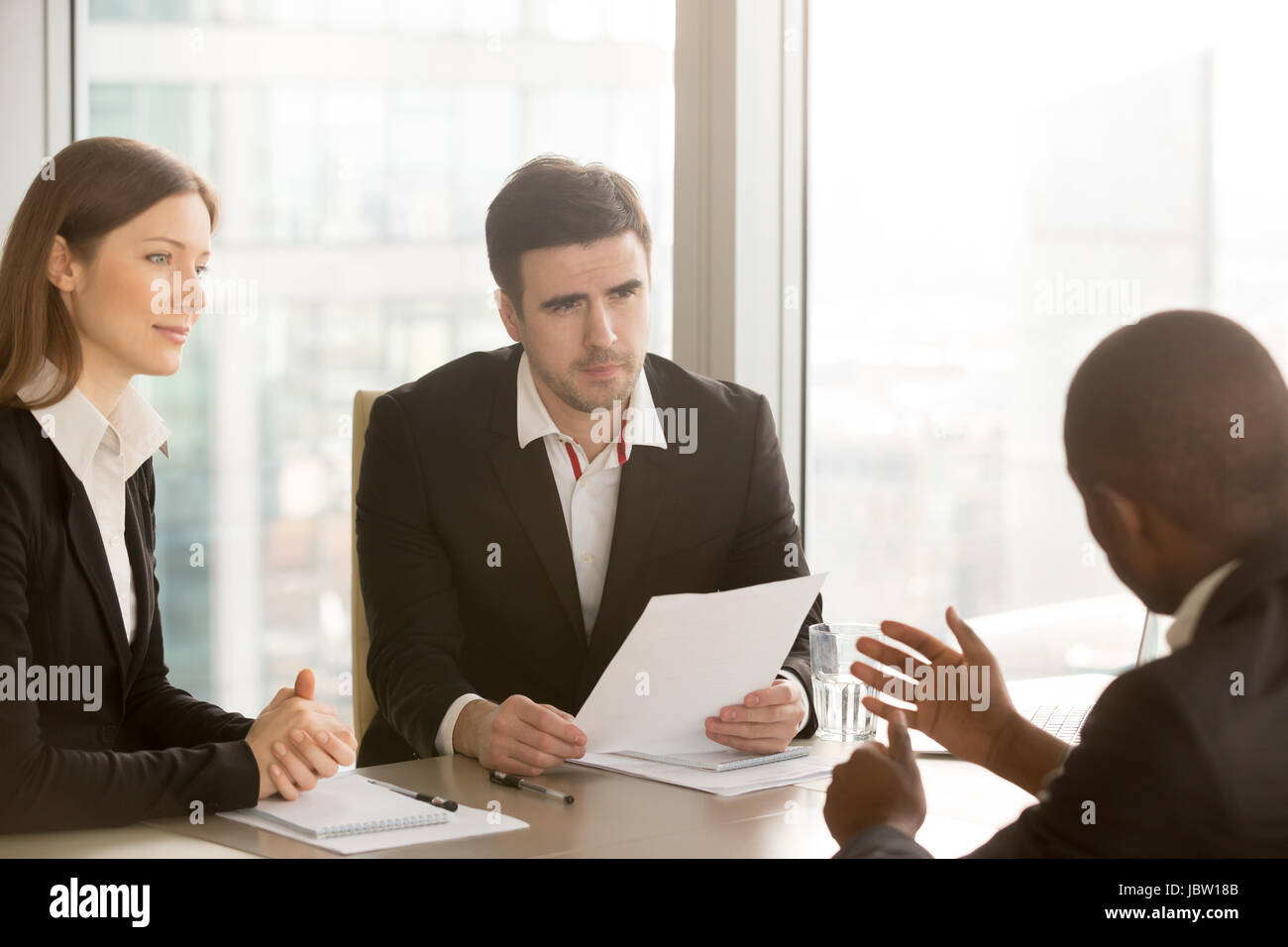 Black businessman trying to convince white doubtful partners to sign document, negotiations about contract, discussing - Stock Image
