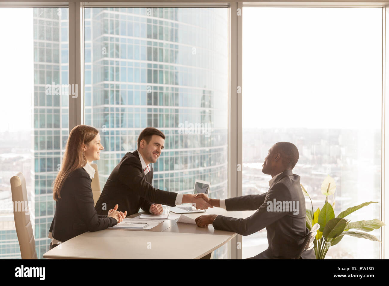 Friendly caucasian employers and confident african-american applicant handshaking during job interview sitting at - Stock Image