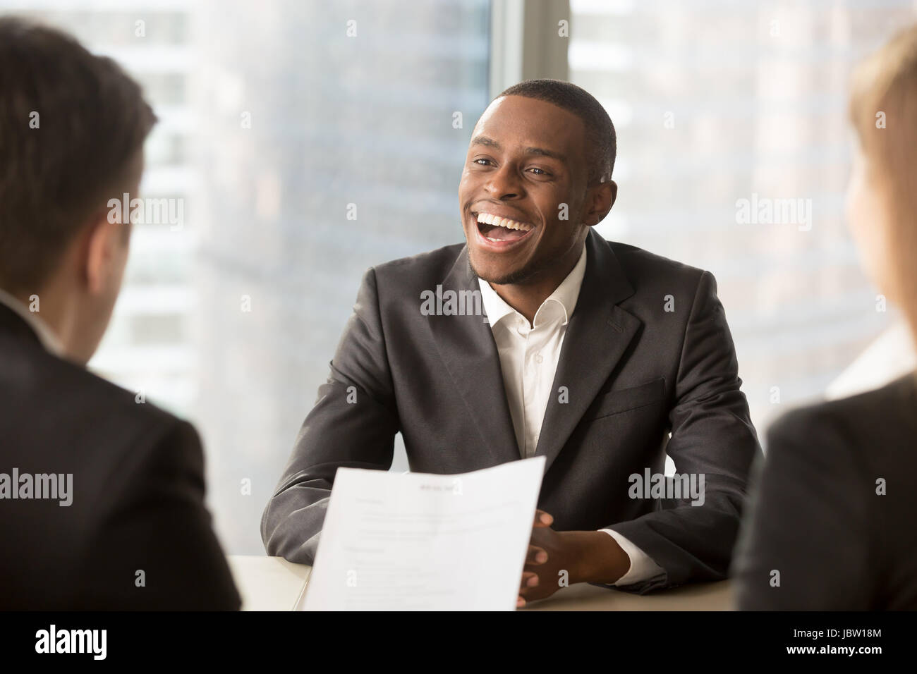 Happy black successful candidate getting hired, cheerful african applicant with beaming smile got a dream job in - Stock Image