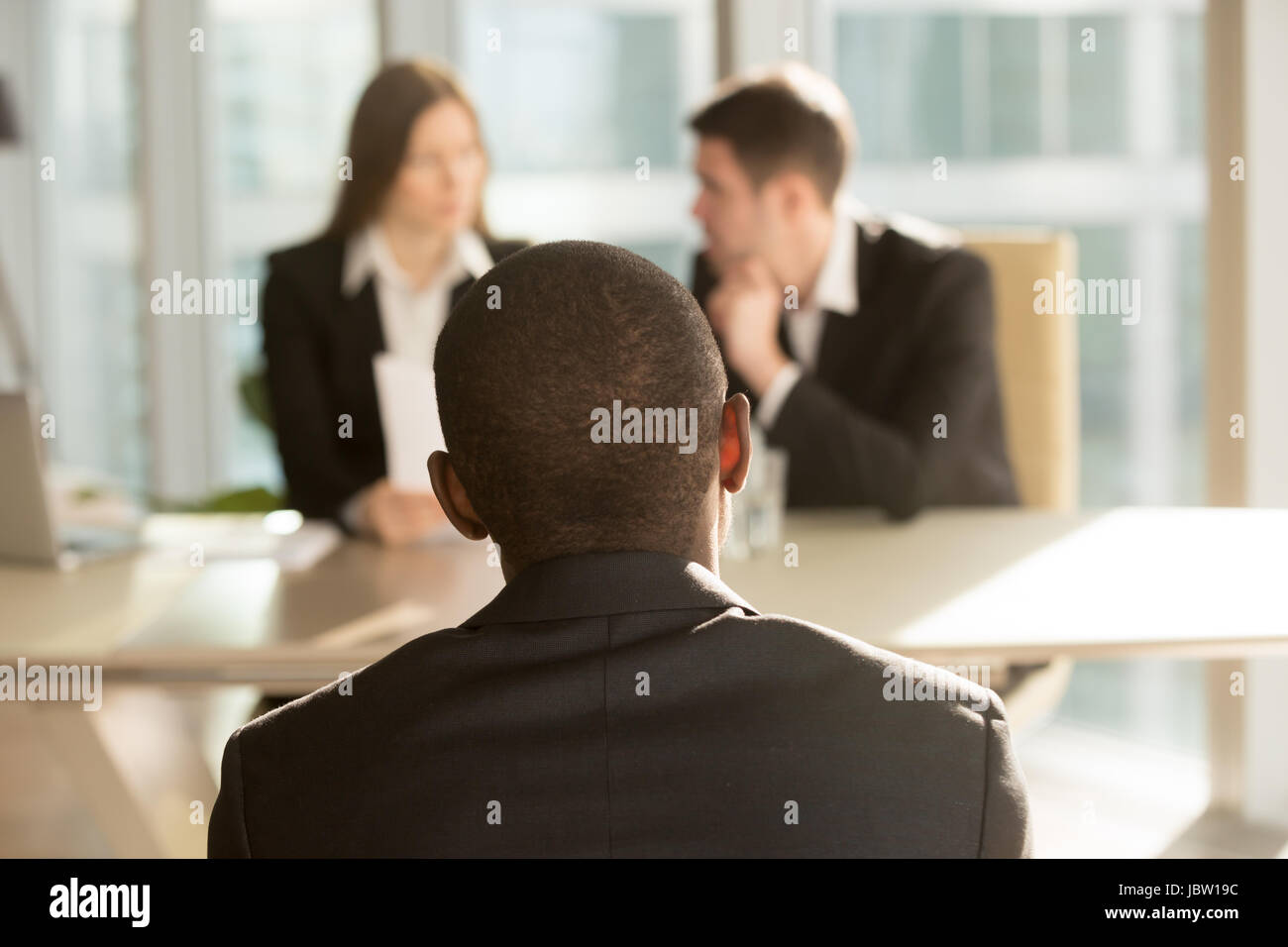 Nervous african-american applicant waiting for result after job interview, hr managers making decision at background, - Stock Image