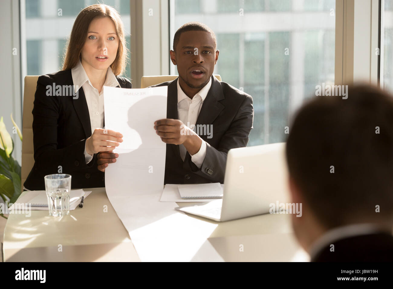 Multiracial recruiters holding long sheet of paper, looking surprisingly at candidate during job interview, prepared - Stock Image
