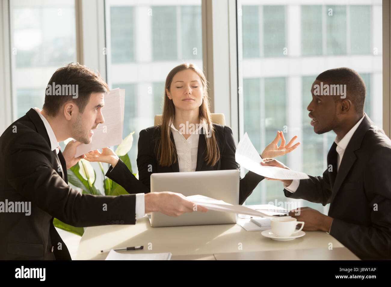 Attractive businesswoman enjoys meditating during meeting, sitting at office desk with eyes closed near arguing - Stock Image