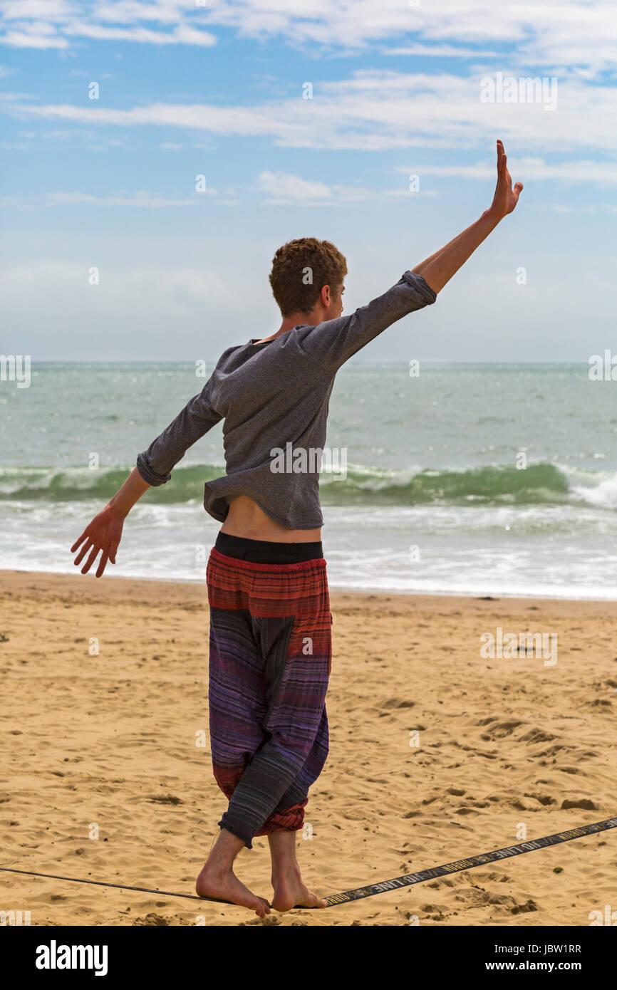 Man on gibbon jibline slackline slacklining balancing act at Bournemouth beach, Dorset in June - Stock Image