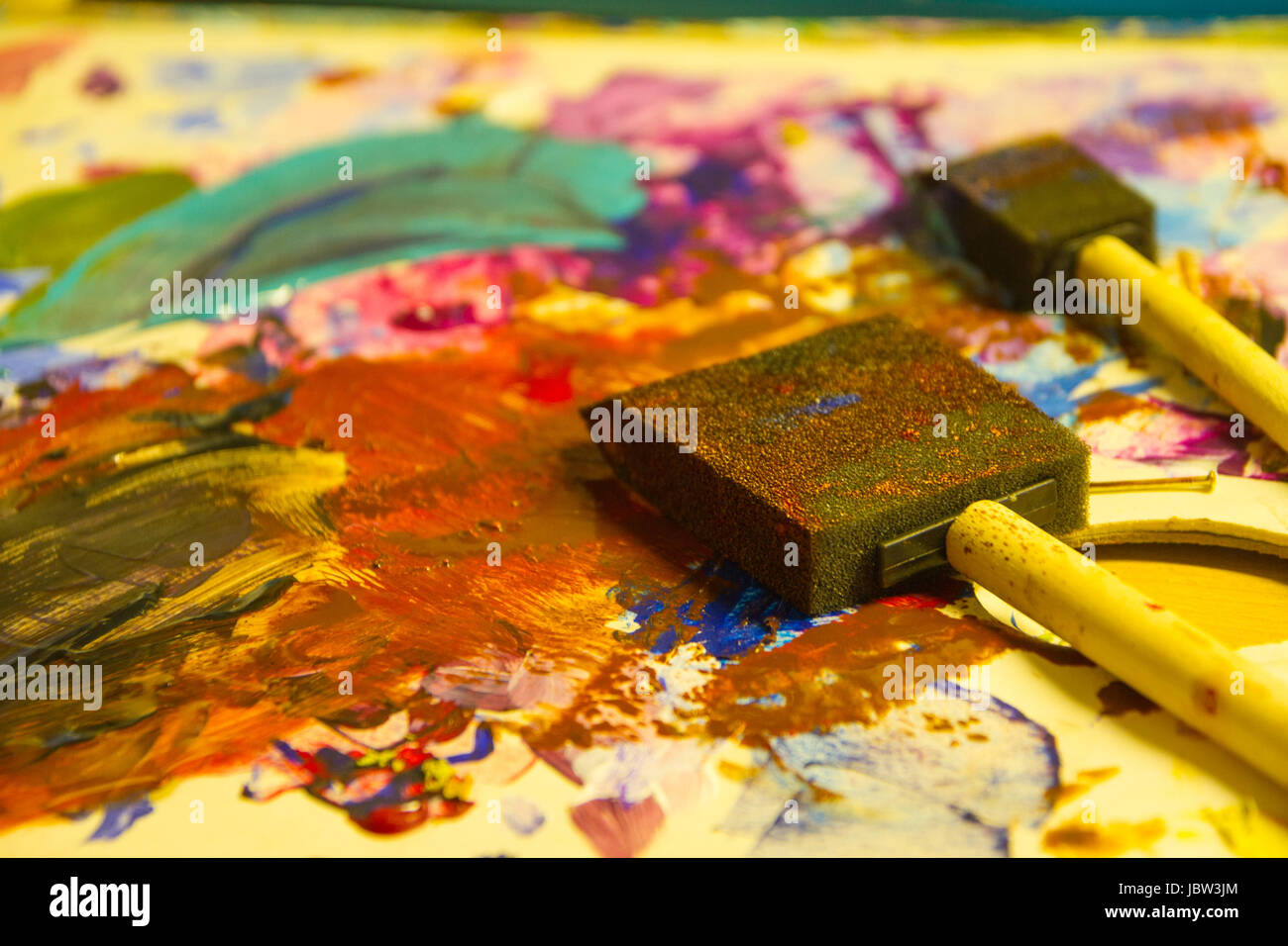 Artiste painting with sponge brushes deposited on paper - Stock Image