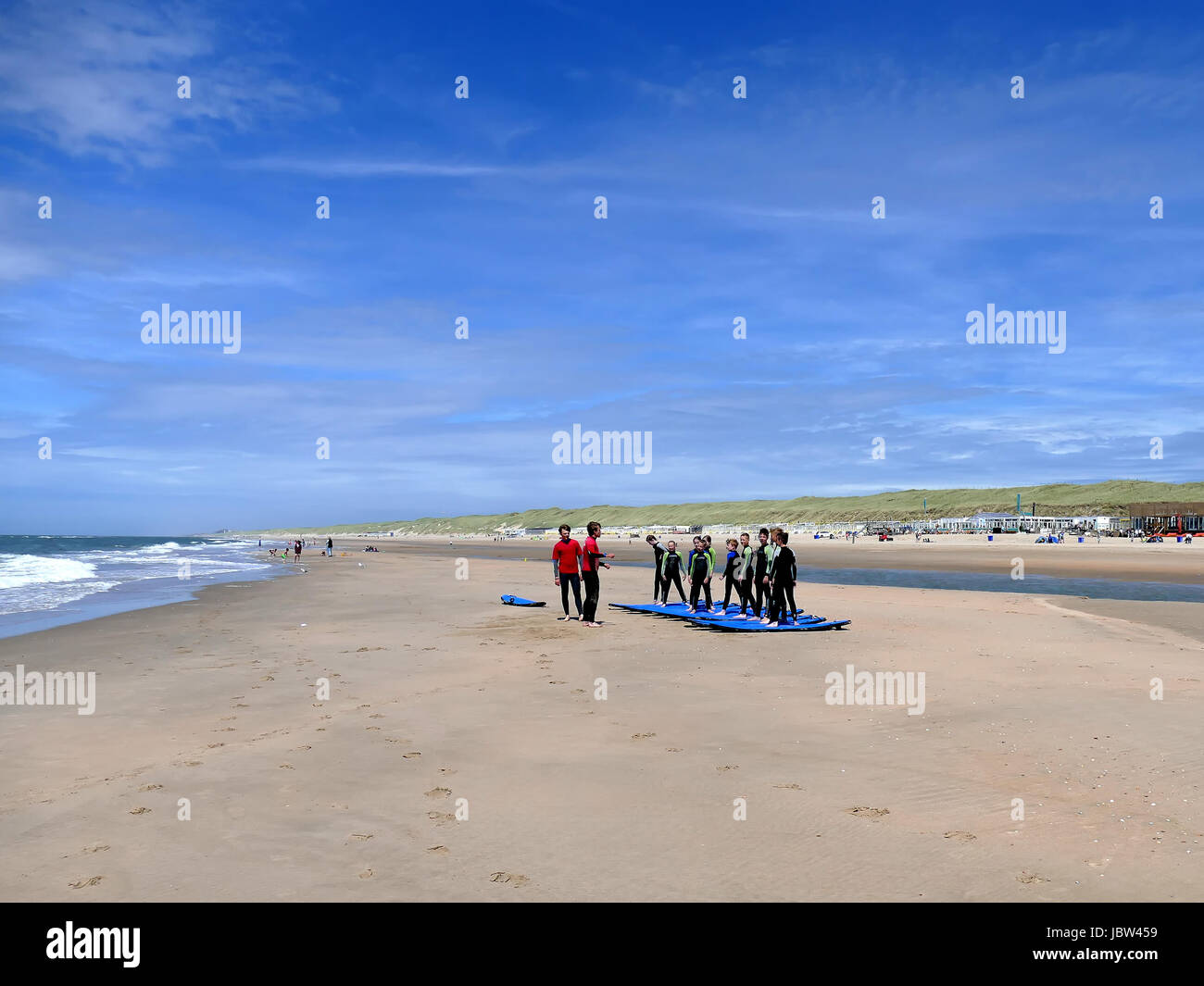 CASTRICUM, THE NETHERLANDS - JUNE 10, 2017: Young teenagers having fun with surfing lessons practising on the beach - Stock Image