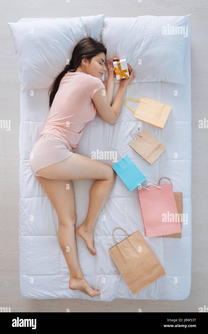 Joyful nice woman sleeping with a present - Stock Image
