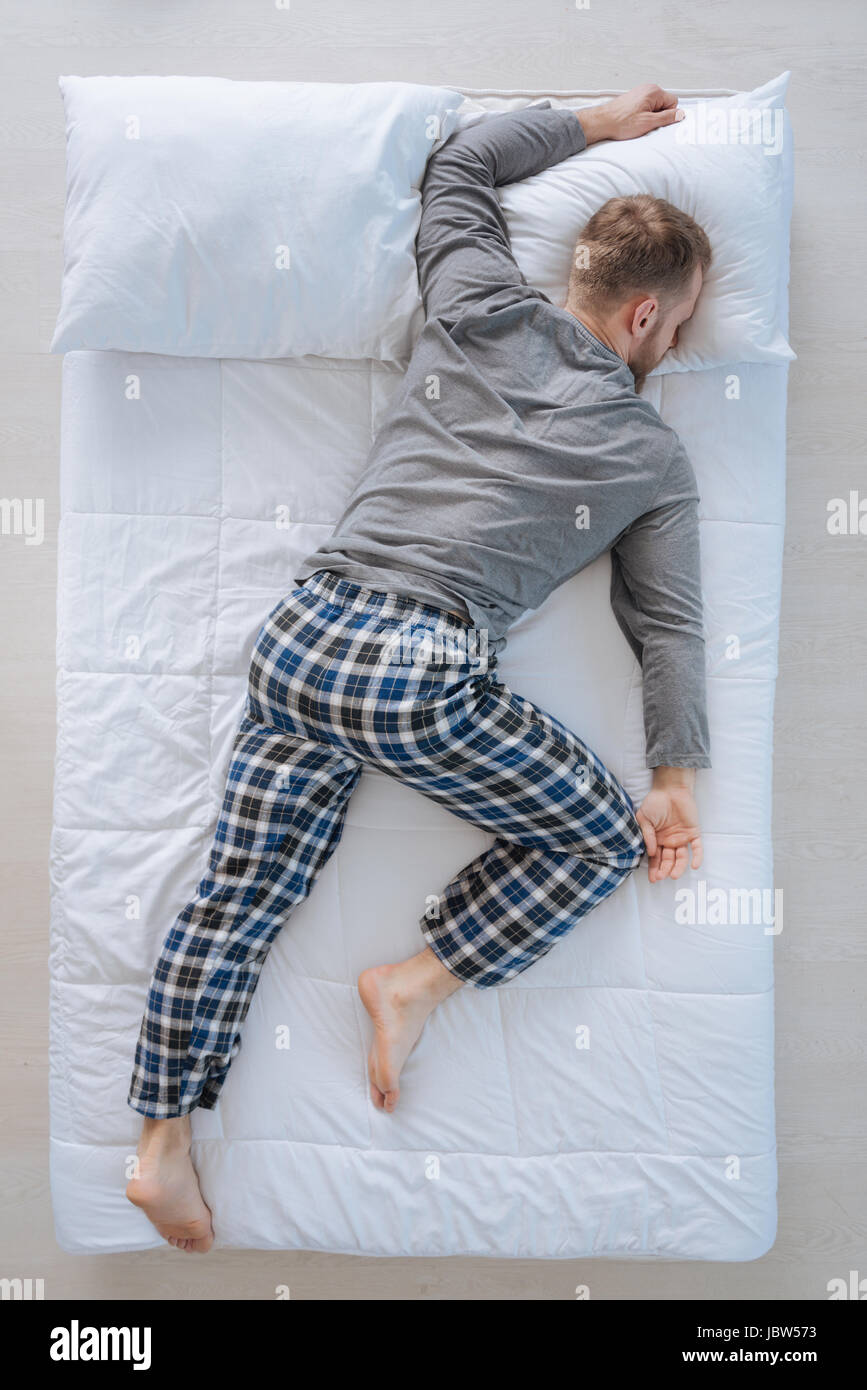 Nice adult man sleeping on his belly - Stock Image