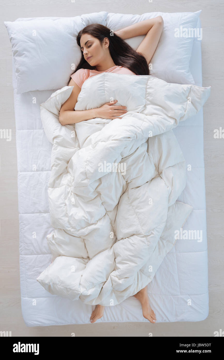 Nice young woman covering herself with the blanket - Stock Image