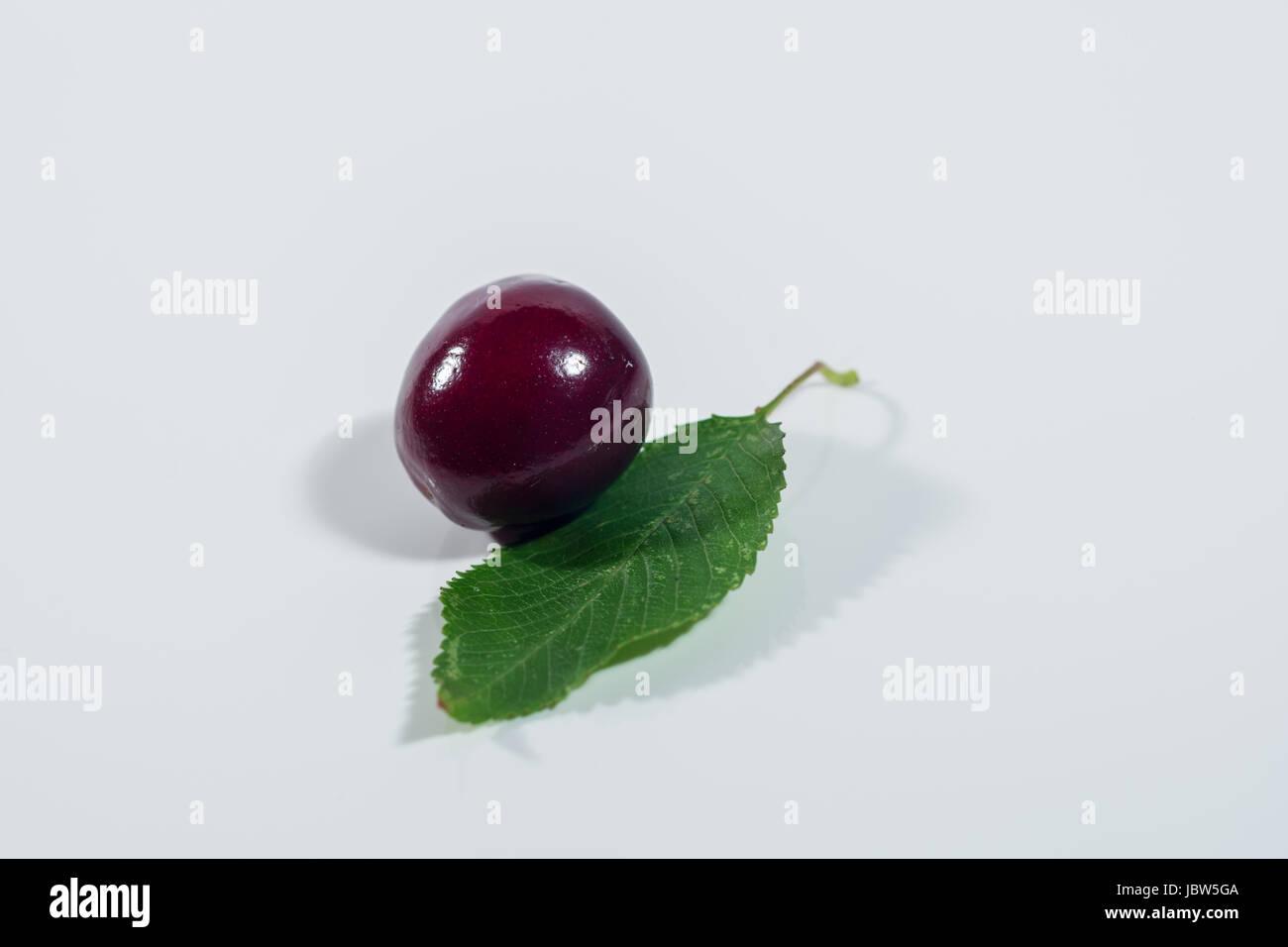 Kirsche mit Blatt auf weißem Hintergrund Stock Photo