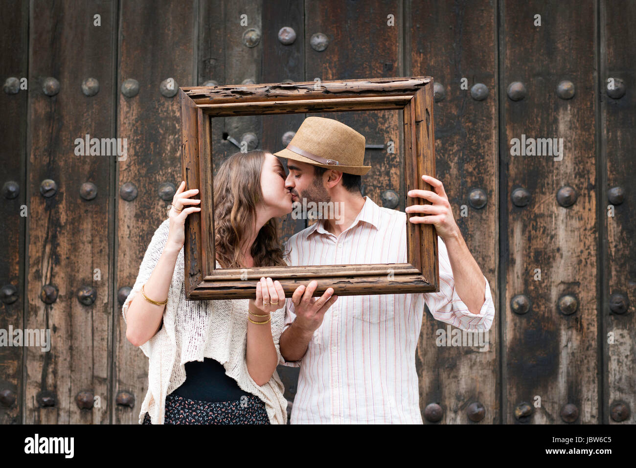Portrait of couple, kissing, holding wooden frame in front of their faces, Mexico City, Mexico - Stock Image