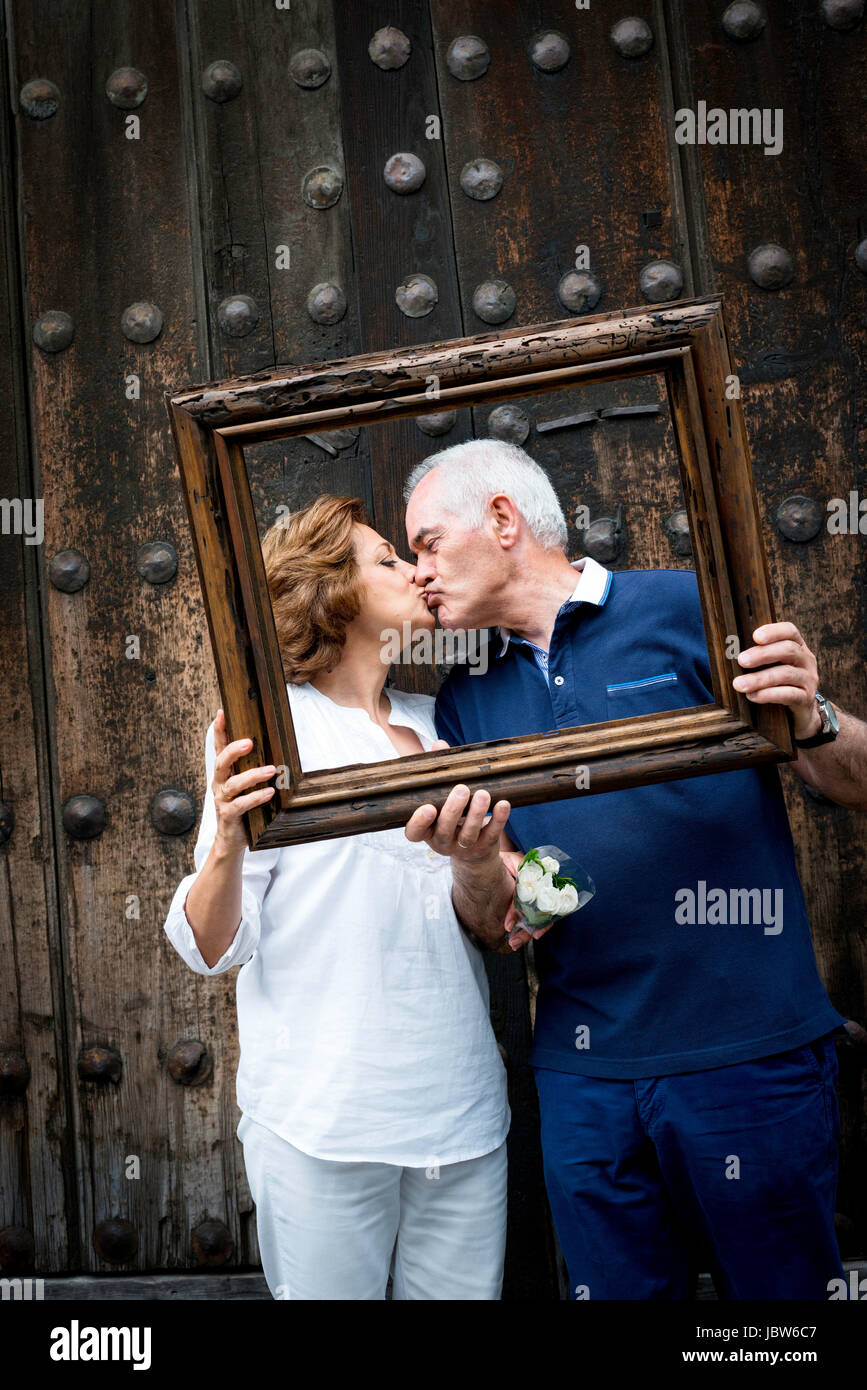 Portrait of senior couple, kissing, holding wooden frame in front of their faces, Mexico City, Mexico - Stock Image