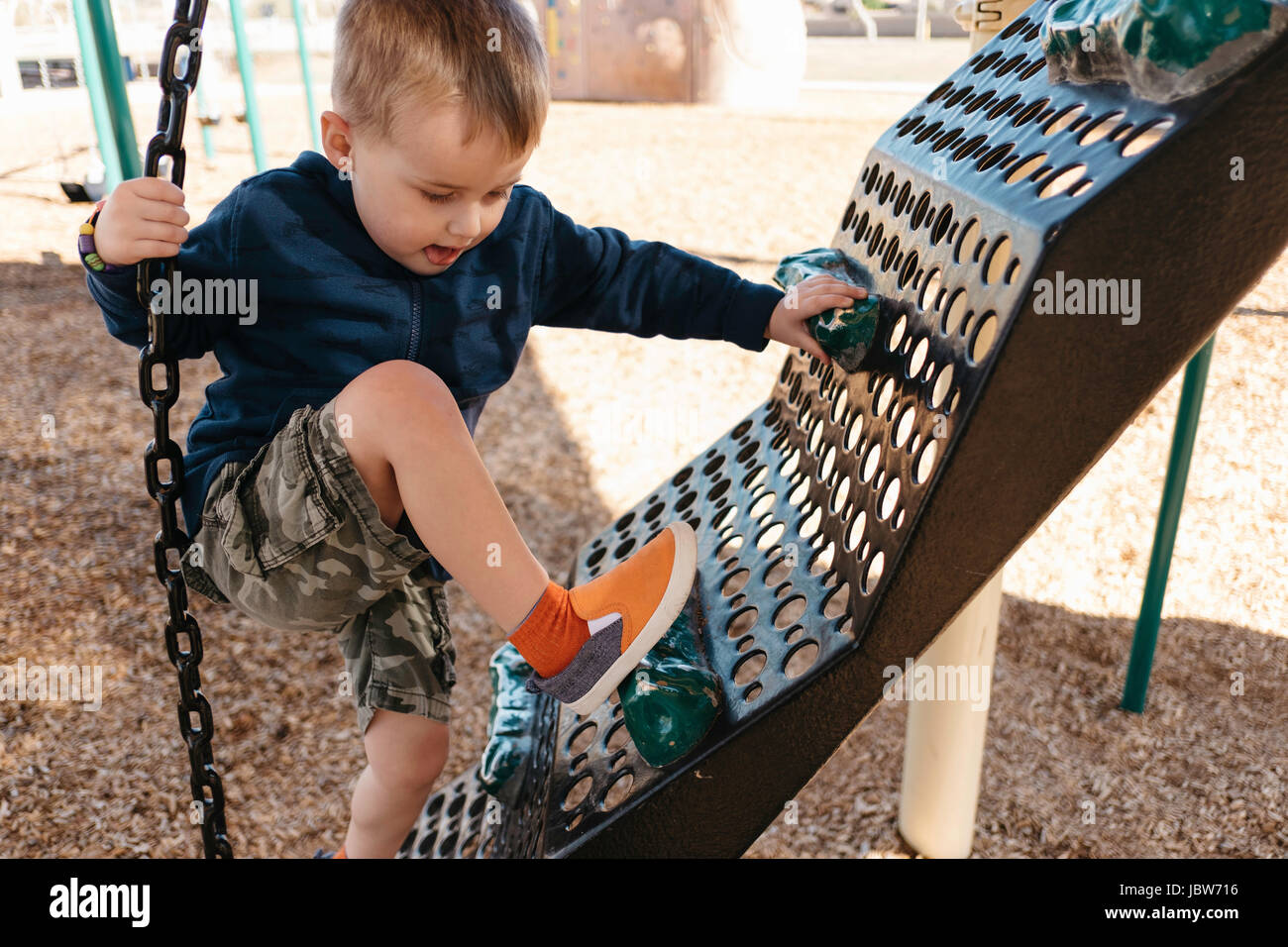 Boy climbing on playground climbing frame - Stock Image