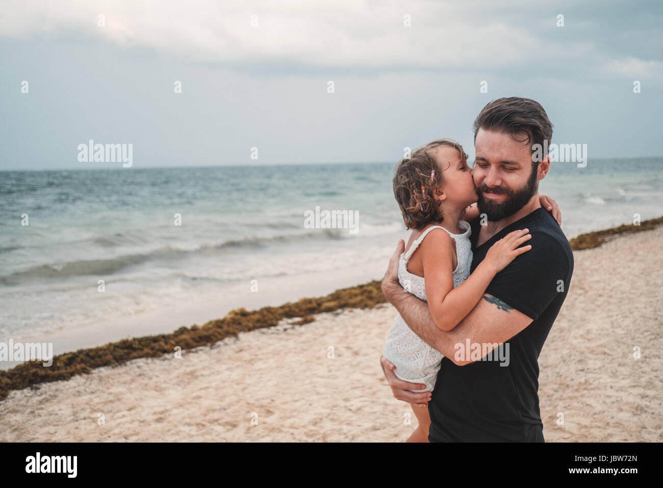 Father kissing daughter on beach, Cancun, Mexico Stock Photo