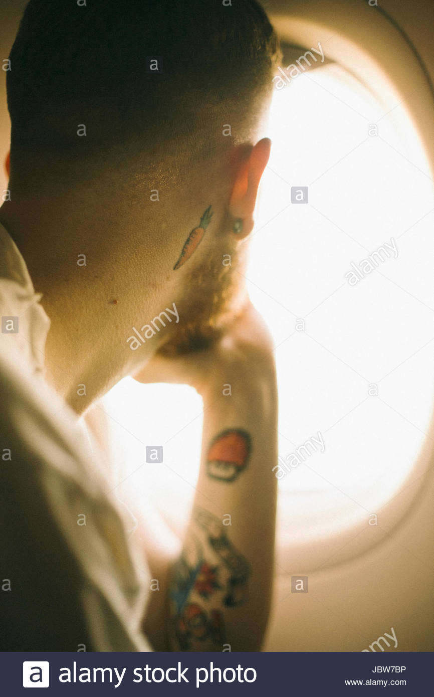 Young man with tattoos, looking out of aeroplane window, rear view - Stock Image