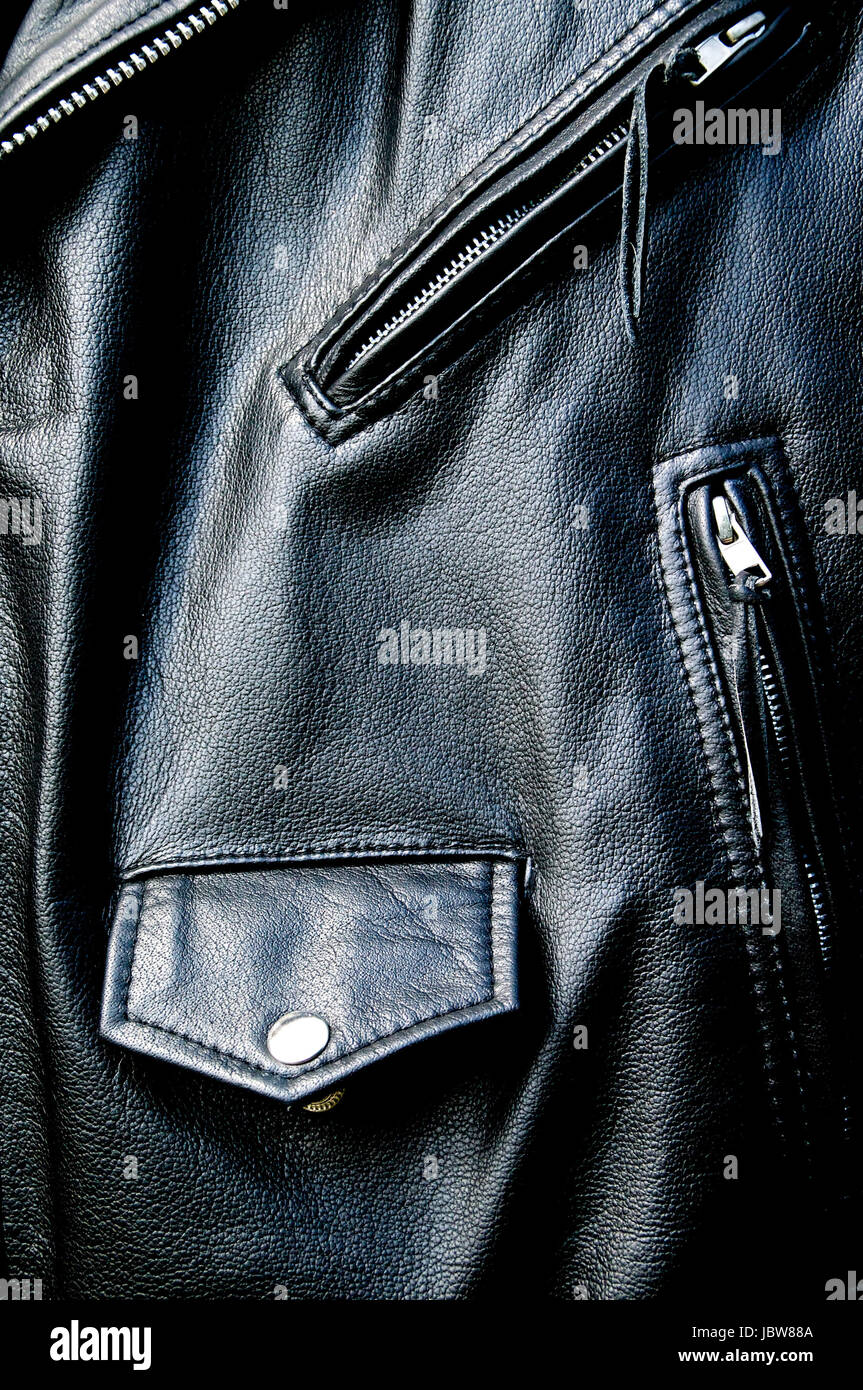 High contrast close up of black leather biker jacket showing zippered pockets and coin pocket with snap button and - Stock Image