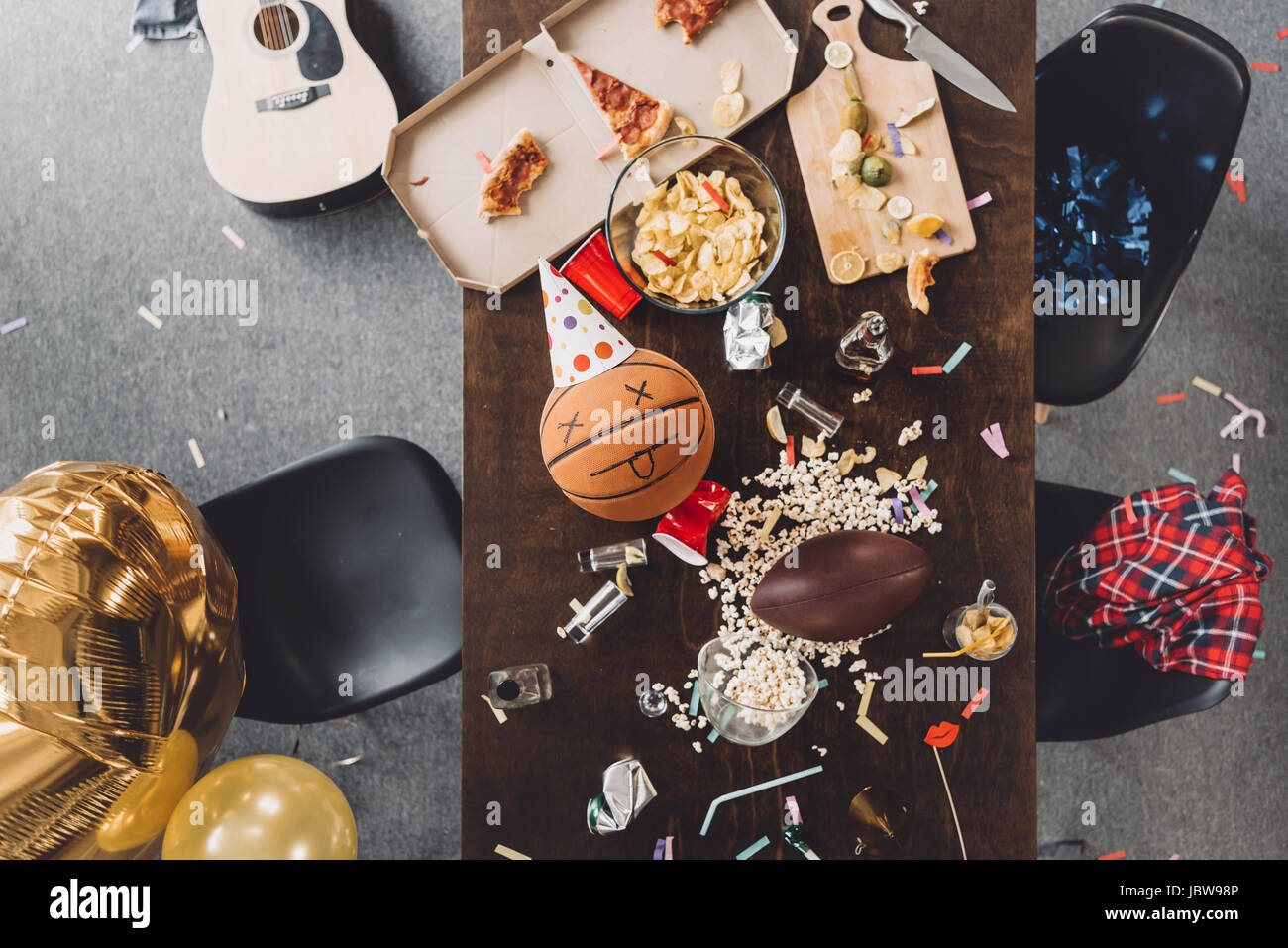 Top view of basketball ball with funny face on messy table after party - Stock Image