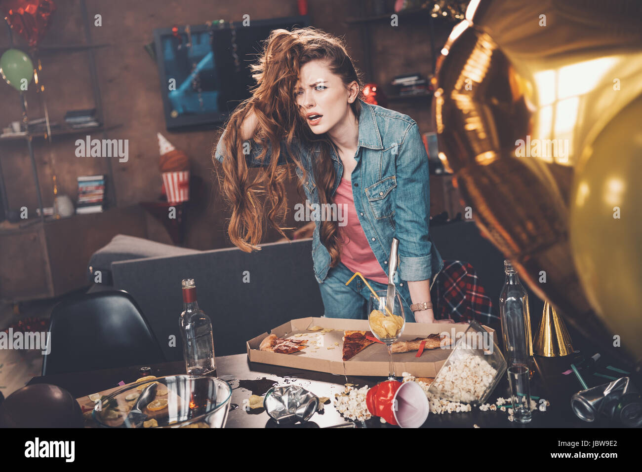 Depressed young woman with hangover leaning at messy table after party Stock Photo