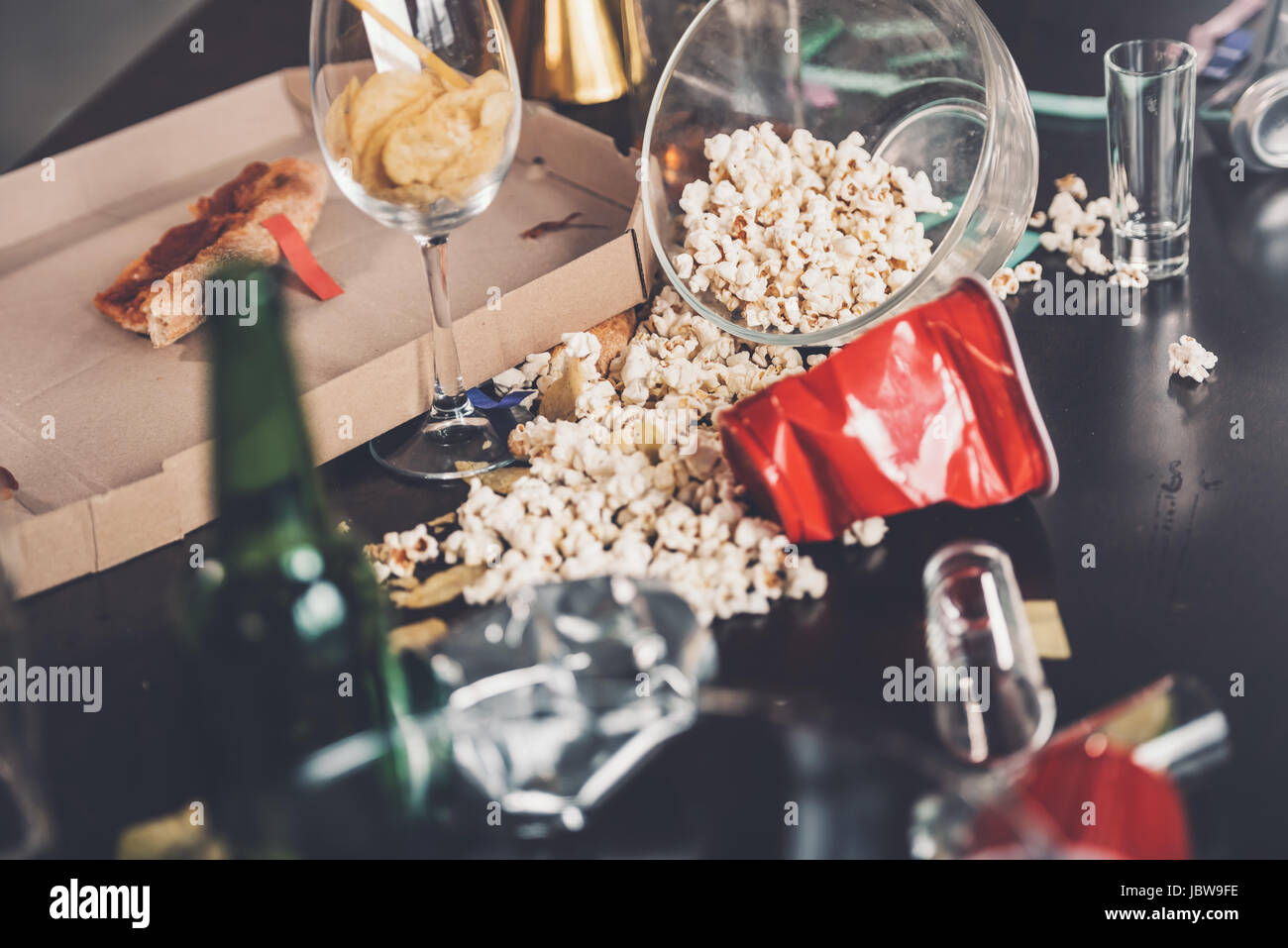 Close-up view of popcorn, glasses and trash on messy table after party - Stock Image