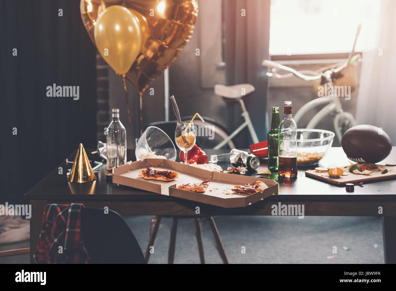 Messy table with pizza in box and beverages at morning after party - Stock Image