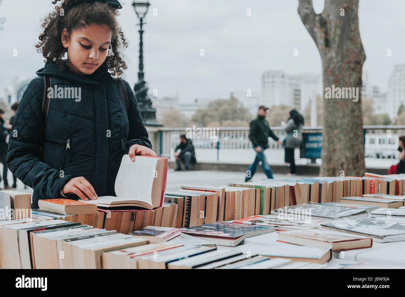 A 10 years old child is browsing second hand books at Southbank Centre Book Market, London. - Stock Image