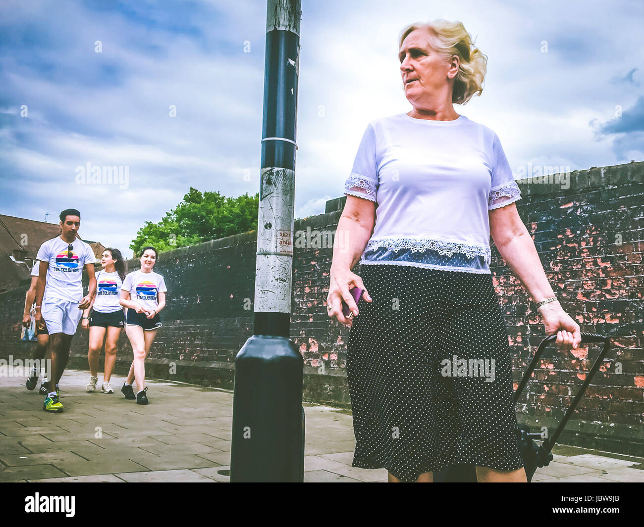 Street photography of a mid-50's woman walking in front of group youngster who is going to the color Run event - Stock Image