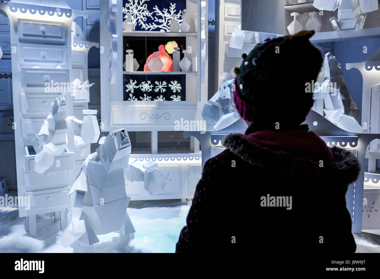 Little girl is looking at Christmas shop window in Paris, France - Stock Image